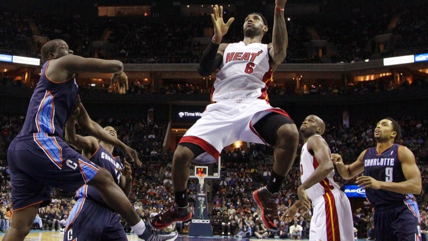 Miami Heat's LeBron James (6) drives to the basket past Charlotte Bobcats' Gerald Henderson (9) and DeSagana Diop (2) during the first half of an NBA basketball game in Charlotte, N.C., Wednesday, Dec. 26, 2012. (AP Photo/Chuck Burton)