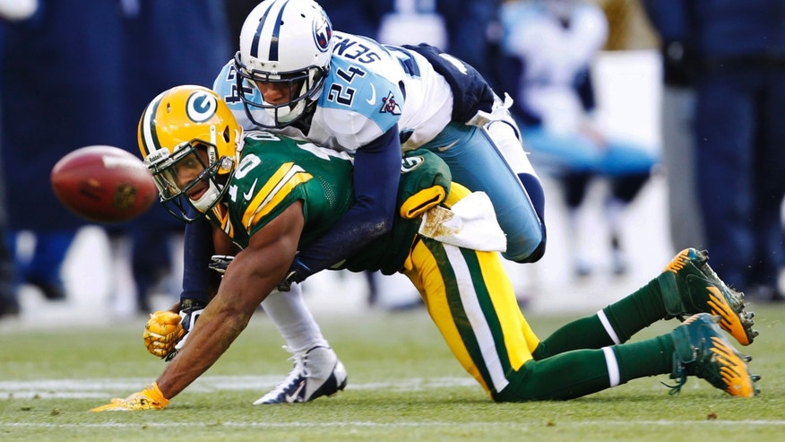 Tennessee Titans' Coty Sensabaugh (24) breaks up a pass intended for Green Bay Packers' Randall Cobb (18) during the first half of an NFL football game Sunday, Dec. 23, 2012, in Green Bay, Wis. (AP Photo/Mike Roemer)