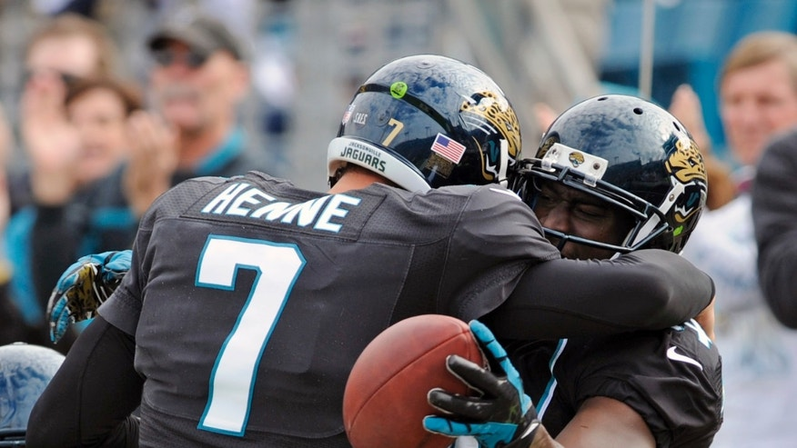 Jacksonville Jaguars quarterback Chad Henne (7) celebrates with wide receiver Justin Blackmon after throwing a touchdown pass to Blackmon against the New England Patriots during the first half of an NFL football game on Sunday, Dec.  23, 2012, in Jacksonville, Fla. (AP Photo/Stephen Morton)