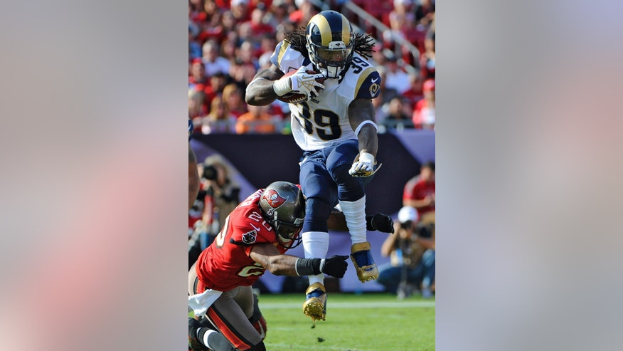 St. Louis Rams running back Steven Jackson (39) leaps away from a hit by Tampa Bay Buccaneers free safety Ronde Barber (20) during the fourth quarter of an NFL football game on Sunday, Dec. 23, 2012, in Tampa, Fla. The Rams won the game 28-13. (AP Photo/Brian Blanco)