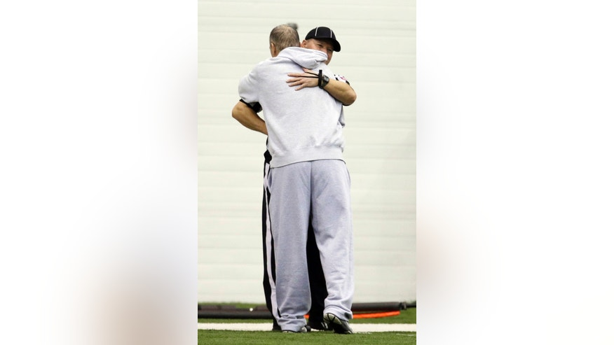 Indianapolis Colts head coach Chuck Pagano is hugged by a college official during NFL football practice at the Colts complex Wednesday, Dec. 26, 2012, in Indianapolis. (AP Photo/Darron Cummings)