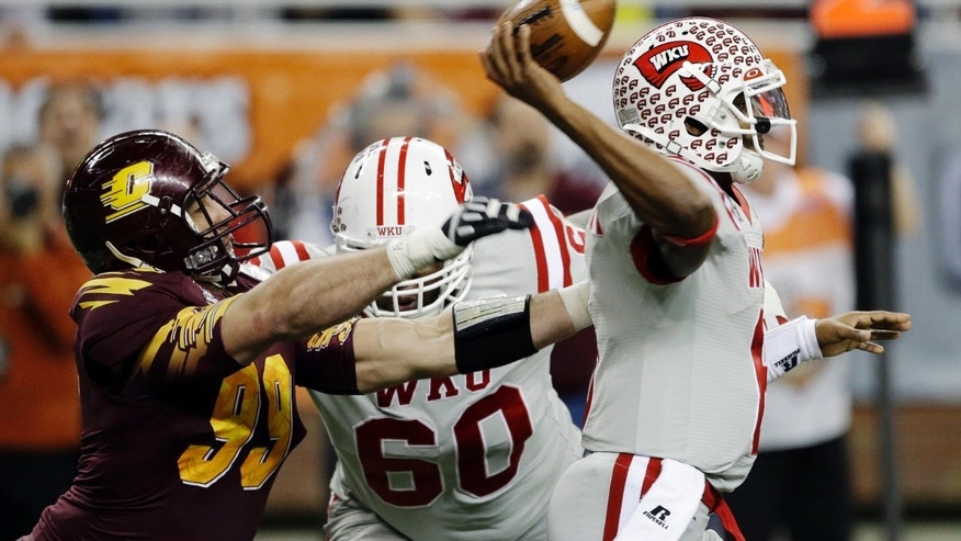 Central Michigan defensive end Caesar Rodriguez (99) closes in on Western Kentucky quarterback Kawaun Jakes (6) during the second quarter of the Little Caesars Pizza Bowl NCAA college football game at Ford Field in Detroit, Wednesday, Dec. 26, 2012. (AP Photo/Carlos Osorio)