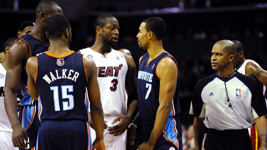 Miami Heat's Dwyane Wade (3) and Charlotte Bobcats' Ramon Sessions (7) interact after Sessions was called for a foul as referee Zach Zarba (33) watches during the second half of their NBA basketball game, Wednesday, Dec. 26, 2012, in Charlotte. The Heat won 105-92. (AP Photo/The Charlotte Observer, David T. Foster III) MAGS OUT; TV OUT; NEWSPAPER INTERNET ONLY