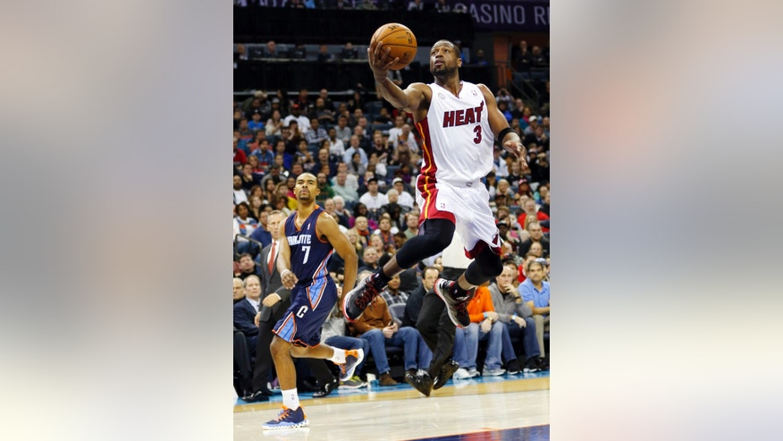 Miami Heat's Dwyane Wade (3) drives past Charlotte Bobcats' Ramon Sessions (7) after being fouled during the second half of an NBA basketball game in Charlotte, N.C., Wednesday, Dec. 26, 2012. Miami won 105-92. (AP Photo/Chuck Burton)