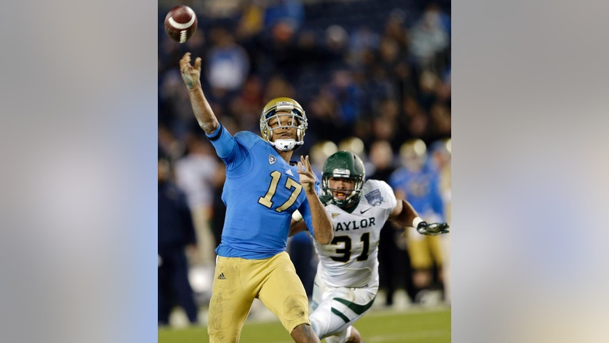 UCLA quarterback Brett Hundley throws a touchdown pass as Baylor's Josh Wilson trails during the second half of the Holiday Bowl NCAA college football game on Thursday, Dec. 27, 2012 in San Diego. Baylor won 49-26. (AP Photo/Lenny Ignelzi)