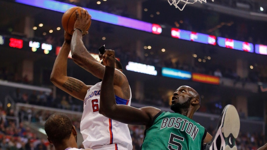 Los Angeles Clippers' DeAndre Jordan, top left, grabs a rebound against Boston Celtics' Kevin Garnett in the first half of an NBA basketball game in Los Angeles, Thursday, Dec. 27, 2012. (AP Photo/Jae C. Hong)