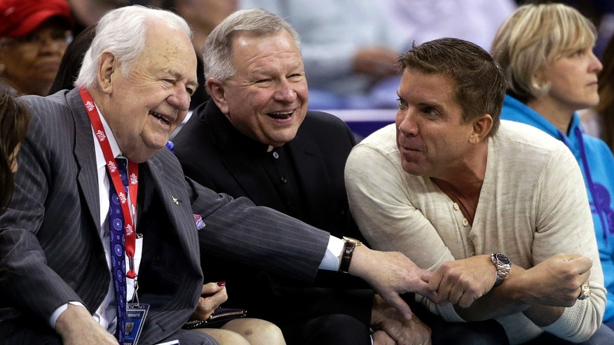 Suspended New Orleans Saints NFL football coach Sean Payton, right, holds hands with Saints owner Tom Benson during the third quarter of an NBA basketball game between the New Orleans Hornets and the Toronto Raptors at the New Orleans Arena in New Orleans, Friday, Dec. 28, 2012. At center is New Orleans Arch Bishop Gregory Aymond. Payton has agreed in principle to a multiyear contract extension, according to two people familiar with the deal. (AP Photo/Dave Martin)
