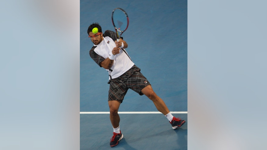 Serbia's Janko Tipsarevic returns the ball to Spain's Nicolas Almagro during the second day of  Mubadala Tennis Championship in Abu Dhabi, United Arab Emirates, Friday, Dec. 28, 2012. (AP Photo/Kamran Jebreili)