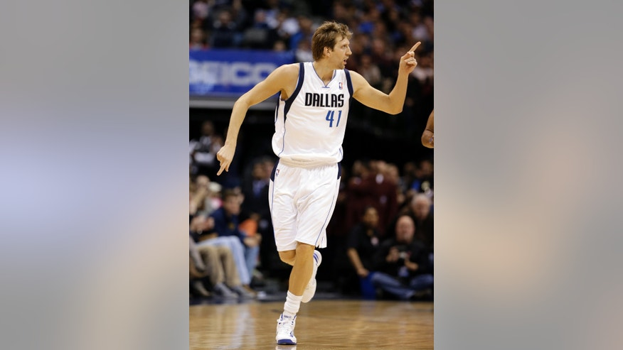 Dallas Mavericks power forward Dirk Nowitzki (41), of Germany, gestures to a teammate after scoring a basket in the first half of an NBA basketball game against the Denver Nuggets, Friday, Dec. 28, 2012, in Dallas. The game is Nowitzki's first at home this season since returning from knee surgery. (AP Photo/Tony Gutierrez)