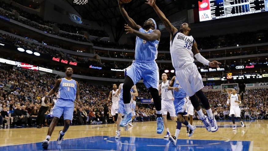 Denver Nuggets small forward Jordan Hamilton, left, watches as point guard Ty Lawson (3) goes up for a shot-attempt as Dallas Mavericks' O.J. Mayo (32) defends in the first half of an NBA basketball game on Friday, Dec. 28, 2012, in Dallas. (AP Photo/Tony Gutierrez)