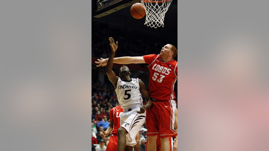 Cincinnati forward Justin Jackson (5) and New Mexico center Alex Kirk (53) go for a rebound during the first half of an NCAA college basketball game, Thursday, Dec. 27, 2012, in Cincinnati. (AP Photo/David Kohl)