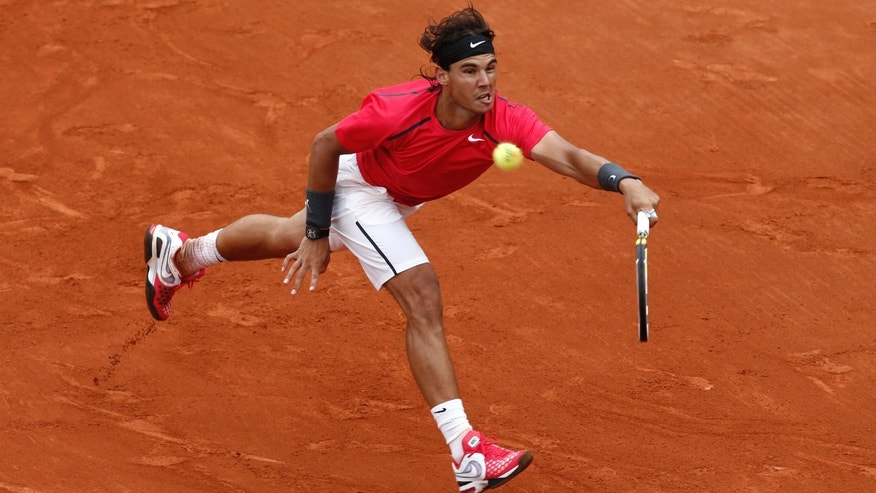 Rafael Nadal returns the ball to compatriot Nicolas Almagro during their quarterfinal match in the French Open tennis tournament at the Roland Garros stadium in Paris, Wednesday, June 6, 2012.