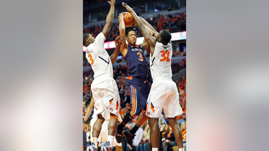 Auburn guard Chris Denson, center, goes up for a shot as Illinois' Brandon Paul, left, and Nnanna Egwu, right, defend during the first half of an NCAA college basketball game in Chicago, Saturday, Dec. 29, 2012. (AP Photo/Nam Y. Huh)