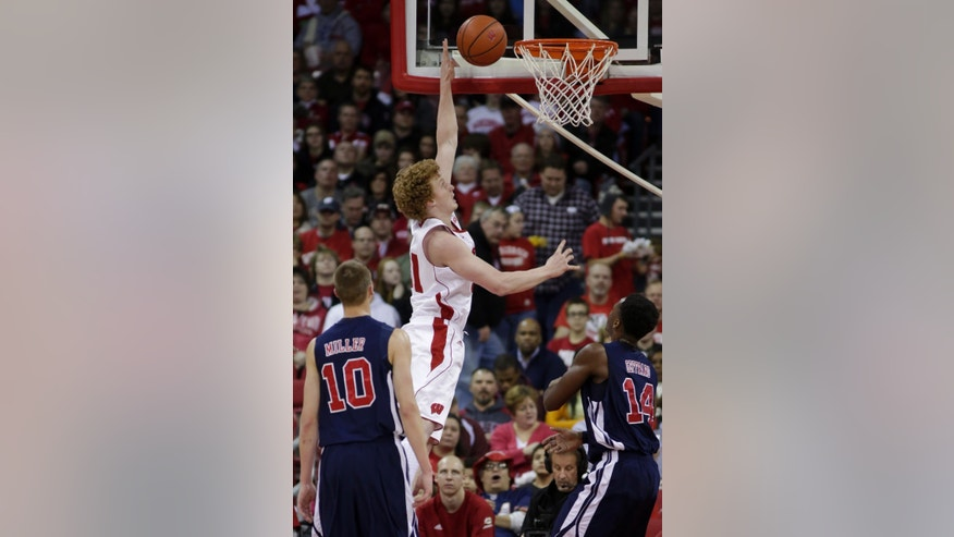 Wisconsin's Mike Bruesewitz, top, dunks over Samford's Conner Miller (10) and Clide Geffrard, Jr., during the first half of an NCAA college basketball game, Saturday, Dec. 29, 2012, in Madison, Wis. (AP Photo/Andy Manis)