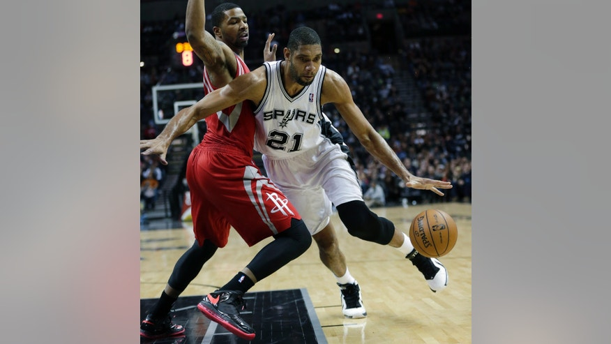 San Antonio Spurs' Tim Duncan (21) works the ball around Houston Rockets' Marcus Morris, left, during the first quarter of an NBA basketball game on Friday, Dec. 28, 2012, in San Antonio. (AP Photo/Eric Gay)