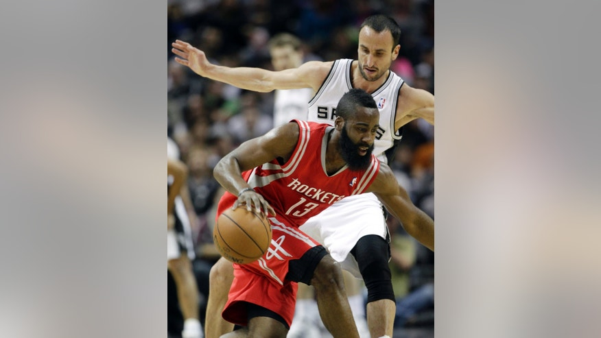 Houston Rockets' James Harden (13) tries ot move the ball around San Antonio Spurs' Manu Ginobili, right, of Argentina, during the first quarter of an NBA basketball game on Friday, Dec. 28, 2012, in San Antonio. (AP Photo/Eric Gay)