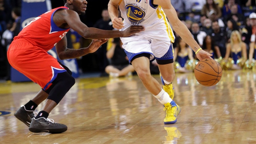 Golden State Warriors' Stephen Curry (30) drives against Philadelphia 76ers' Jrue Holiday (11) during the second half of an NBA basketball game in Oakland, Calif., Friday, Dec. 28, 2012. Golden State won 96-89.  (AP Photo/Marcio Jose Sanchez)