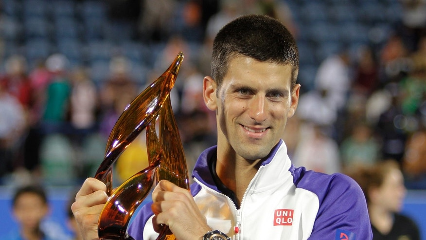 Serbia's Novak Djokovic holds the trophy after he beats Spain's Nicolas Almagro in the final match of the Mubadala Tennis Championship in Abu Dhabi, United Arab Emirates, Saturday, Dec. 29, 2012. (AP Photo/Kamran Jebreili)