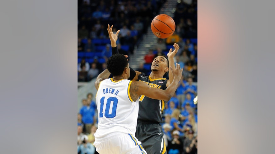 Missouri's Phil Pressey, right, and UCLA's Larry Drew II fight for a loose ball during the first half of an NCAA college basketball game in Los Angeles, Friday, Dec. 28, 2012. (AP Photo/Jae C. Hong)
