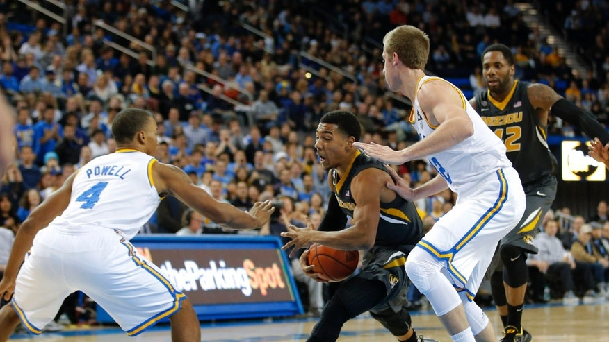 Missouri's Phil Pressey, center, is defended by UCLA's Norman Powell, left, and David Wear during the first half of an NCAA college basketball game in Los Angeles, Friday, Dec. 28, 2012. (AP Photo/Jae C. Hong)
