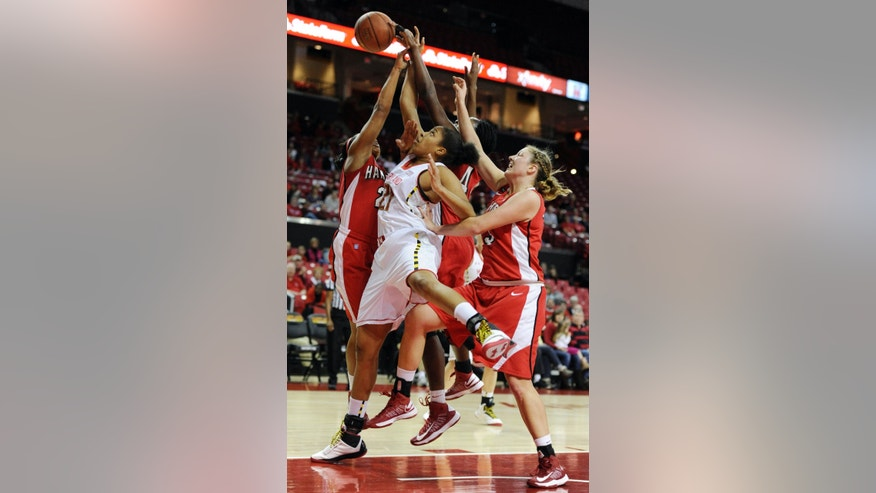 Maryland's Tianna Hawkins, center, battles Hartford players Daphne Elliott, left, Nikkia Smith, partially blocked, and Taylor Clark, right, for the ball in the first half of an NCAA college basketball game Saturday, Dec. 29, 2012 in College Park, Md. (AP Photo/Gail Burton).
