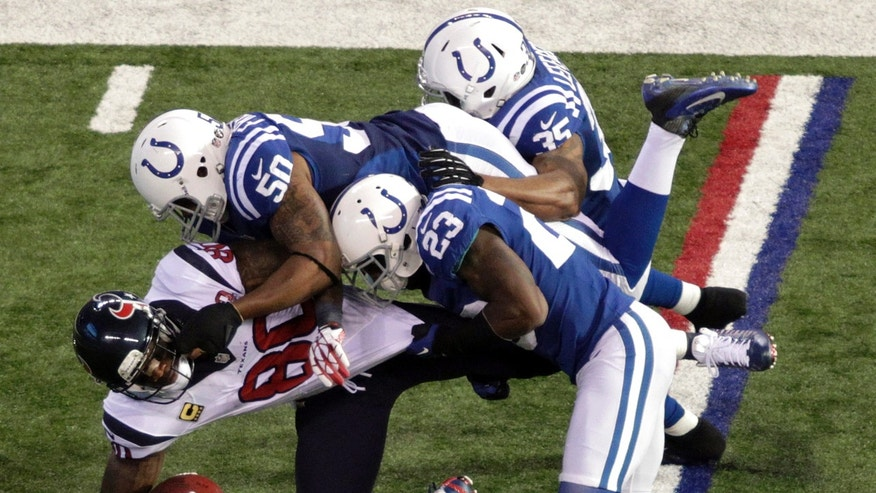Houston Texans' Andre Johnson (80) is tackled by Indianapolis Colts' Jerrell Freeman (50), Vontae Davis (23) and Joe Lefeged (35) during the second half of an NFL football game, Sunday, Dec. 30, 2012, in Indianapolis. (AP Photo/AJ Mast)