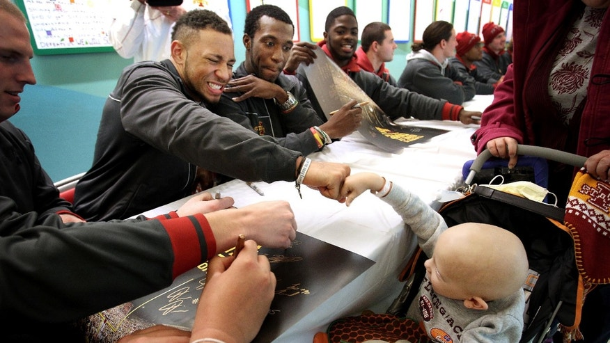 St. Jude patient Johnah Sahr, lower right, 4, dishes out a powerful fist bump to Iowa State strong safety Jared Brackens as he gets an autographed poster from the team  Thursday, Dec. 27, 2012, in Memphis, Tenn. Team members from both Iowa State and Tulsa, who are scheduled to meet in the NCAA college football Liberty Bowl, on Monday, toured St. Jude and met with patients Thursday.  (AP Photo/The Commercial Appeal, Mike Brown)