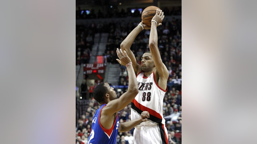 Portland Trail Blazers forward Nicolas Batum, right, from France, looks to pass inside against Philadelphia 76ers guard Evan Turner during the second half of an NBA basketball game in Portland, Ore., Saturday, Dec. 29, 2012.  Batum led the Trail Blazers with 22 points as they defeated the 76ers 89-85.(AP Photo/Don Ryan)