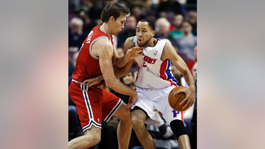 Detroit Pistons forward Tayshaun Prince (22) takes a hit in the throat from Milwaukee Bucks forward Mike Dunleavy while going to the basket in the first half of an NBA basketball game, Sunday, Dec. 30, 2012, in Auburn Hills, Mich. (AP Photo/Duane Burleson)
