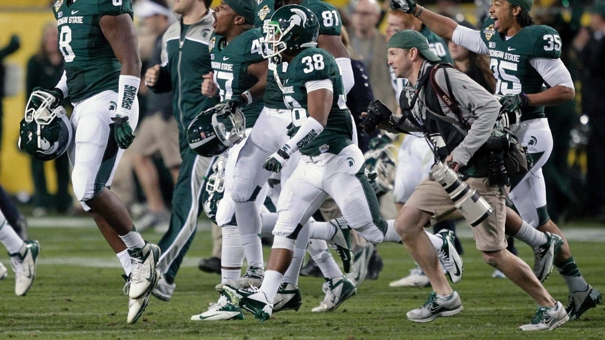 Michigan State players celebrate on the field after winning the Buffalo Wild Wings Bowl NCAA college football game against TCU, Saturday, Dec. 29, 2012, in Tempe, Ariz. Michigan State won 17-16. (AP Photo/Matt York)
