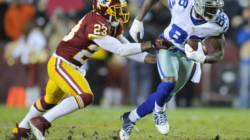 Dallas Cowboys wide receiver Dez Bryant (88) is stopped by Washington Redskins cornerback DeAngelo Hall (23) during the first half of an NFL football game Sunday, Dec. 30, 2012, in Landover, Md. (AP Photo/Nick Wass)