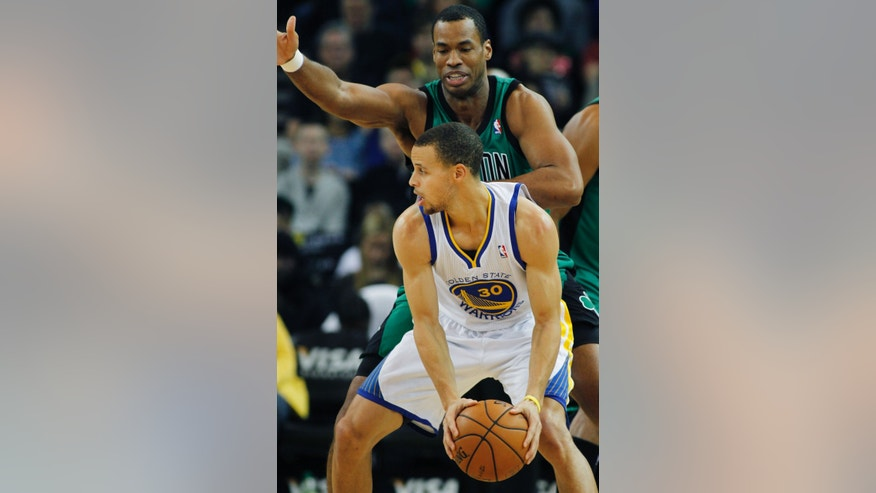 Golden State Warriors' Stephen Curry, foreground, looks for a receiver under the arm of Boston Celtics' Jason Collins during the first half of an NBA basketball game in Oakland, Calif., Saturday, Dec. 29, 2012. (AP Photo/George Nikitin)