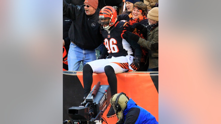 Cincinnati Bengals defensive end Carlos Dunlap (96) celebrates with fans after scoring a touchdown on an interception against the Baltimore Ravens in the second half of an NFL football game, Sunday, Dec. 30, 2012, in Cincinnati. (AP Photo/Tom Uhlman)