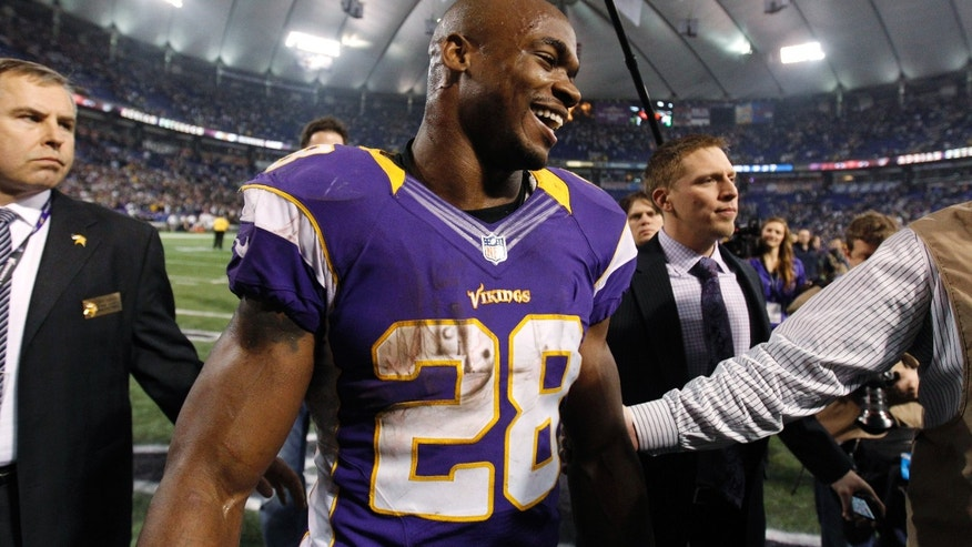 Minnesota Vikings running back Adrian Peterson smiles while walking off the field after the Vikings' NFL football game against the Green Bay Packers on Sunday, Dec. 30, 2012, in Minneapolis.  Peterson rushed for 199 yard as the Vikings won 37-34. (AP Photo/Genevieve Ross)