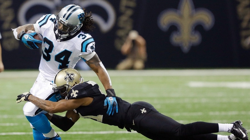 New Orleans Saints' Patrick Robinson tries to stop Carolina Panthers' DeAngelo Williams (34) on a run  during the first half of an NFL football game Sunday, Dec. 30, 2012, in New Orleans. (AP Photo/Bill Haber)