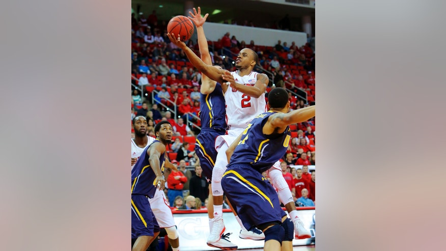 North Carolina State's Lorenzo Brown (2) drives to the basket between UNC-Greensboro's Kelvin McNeil, right, and Jordan Potts, center, during the first half of an NCAA college basketball game in Raleigh, N.C., Monday, Dec. 31, 2012. (AP Photo/Ted Richardson)
