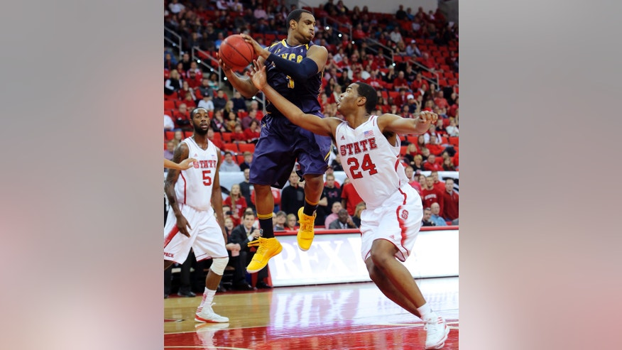 UNC-Greensboro's Derrell Armstrong, center, keeps the ball from North Carolina State's T.J. Warren (24) during the first half of an NCAA college basketball game in Raleigh, N.C., Monday, Dec. 31, 2012. (AP Photo/Ted Richardson)