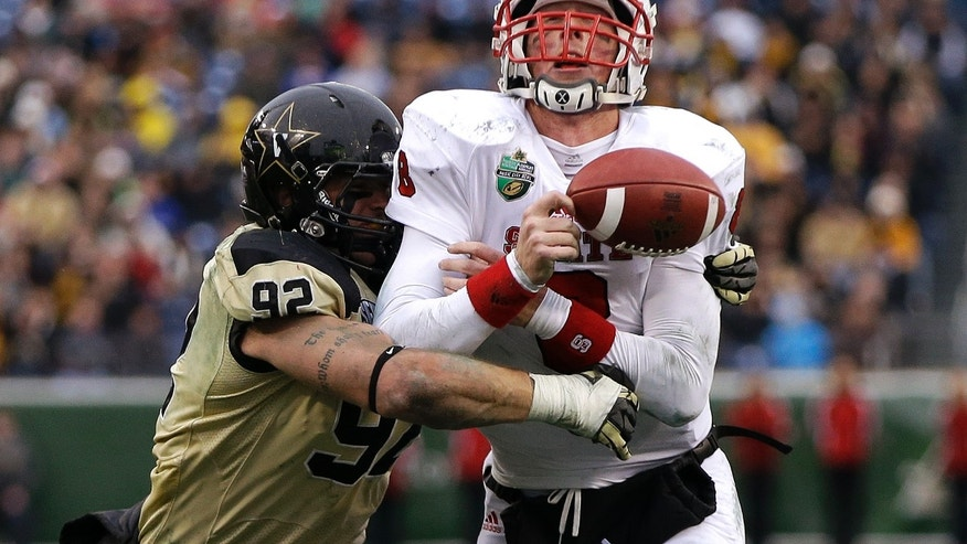Vanderbilt defensive end Kyle Woestmann (92) knocks the ball out of the grasp of North Carolina State quarterback Mike Glennon (8) in the third quarter of the Music City Bowl NCAA college football game, Monday, Dec. 31, 2012, in Nashville, Tenn. North Carolina State recovered the ball on the play and lost 2 yards. (AP Photo/Mark Humphrey)