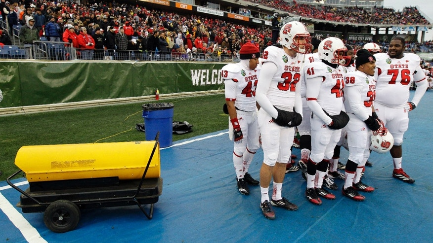 North Carolina State players huddle around a heater in the fourth quarter of the Music City Bowl NCAA college football game against Vanderbilt, Monday, Dec. 31, 2012, in Nashville, Tenn. Vanderbilt won 38-24. (AP Photo/Mark Humphrey)