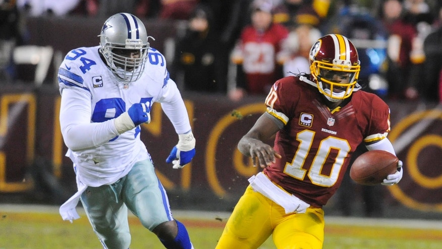 Washington Redskins quarterback Robert Griffin III (10) runs away from Dallas Cowboys outside linebacker DeMarcus Ware (94) during the second half of an NFL football game Sunday, Dec. 30, 2012, in Landover, Md. The Redskins won 28-18. (AP Photo/Richard Lipski)