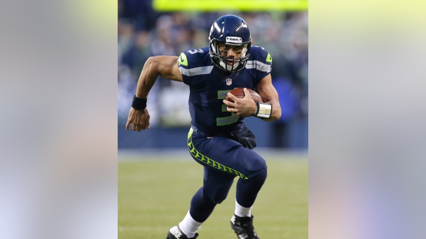 Seattle Seahawks quarterback Russell Wilson keeps the ball and rushes for a 15-yard gain in the second half of an NFL football game, Sunday, Dec. 30, 2012, in Seattle. The Seahawks won 20-13. (AP Photo/Elaine Thompson)