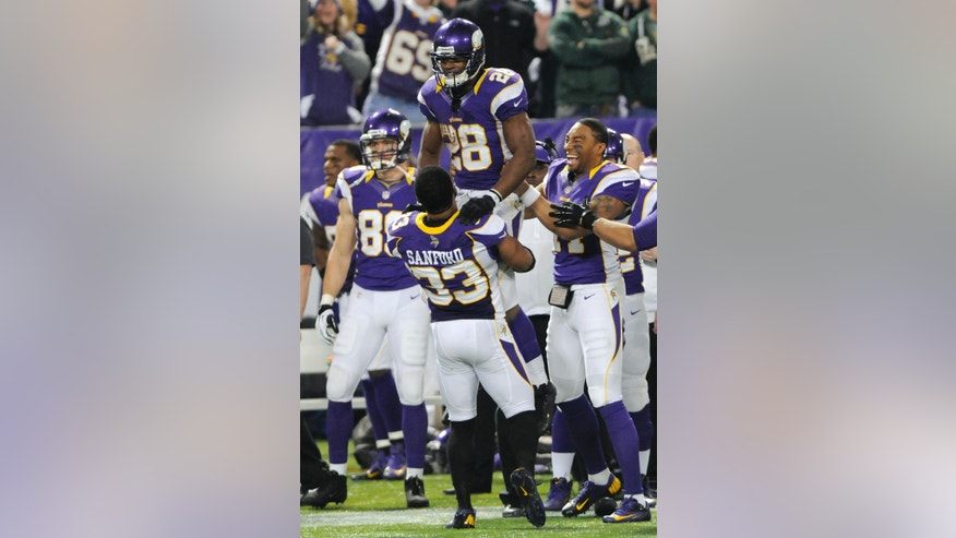 Minnesota Vikings running back Adrian Peterson, top, celebrates with teammate Jamarca Sanford (33) at the end of an NFL football game against the Green Bay Packers Sunday, Dec. 30, 2012, in Minneapolis. The Vikings won 37-34. (AP Photo/Jim Mone)
