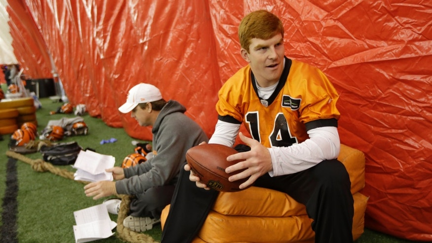 Cincinnati Bengals quarterback Andy Dalton (14) sits near offensive coordinator Jay Gruden, left, during practice under a dome at the University of Cincinnati, Wednesday, Jan. 2, 2013, in Cincinnati. Cincinnati plays at Houston this Saturday in an NFL playoff football game. (AP Photo/Al Behrman)