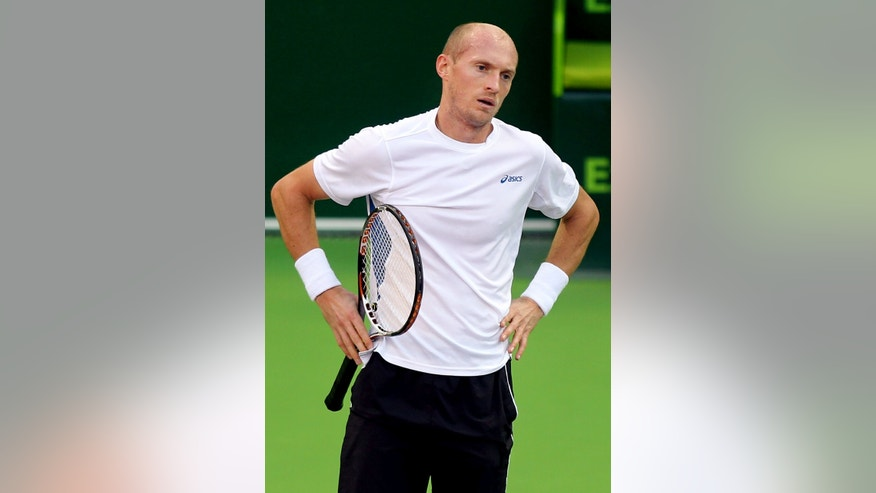 Russia's Nikolay Davydenko reacts after losing a point against Russia's Mikhail Youzhny during the Qatar ATP Open Tennis tournament in Doha, Qatar, Wednesday, Jan. 2, 2013. (AP Photo/Osama Faisal)