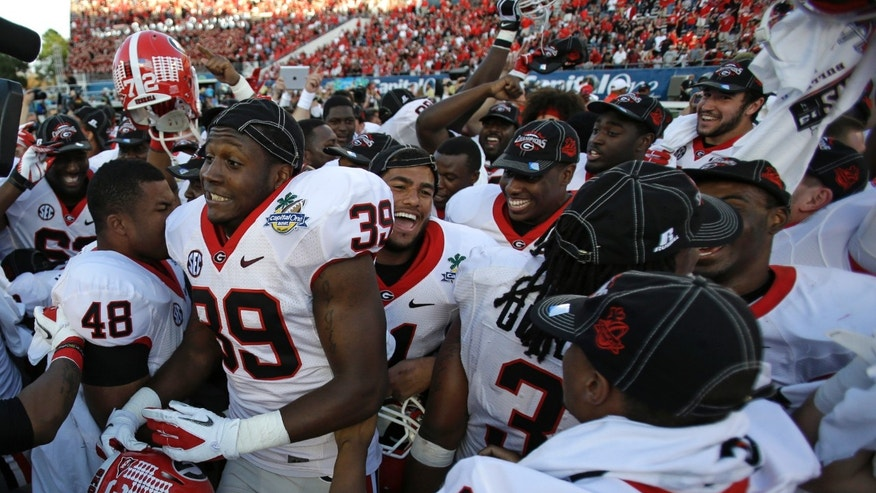 Georgia players including safety Corey Moore (39) and Curtis Wyatt (9) celebrate their 45-31 victory over Nebraska in the Capital One Bowl NCAA football game, Tuesday, Jan. 1, 2013, in Orlando, Fla.(AP Photo/John Raoux)