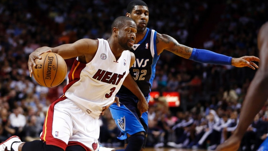 Miami Heat's Dwyane Wade (3) drives around Dallas Mavericks' O.J. Mayo (32) during the first half of an NBA basketball game in Miami, Wednesday, Jan. 2, 2013. (AP Photo/J Pat Carter)
