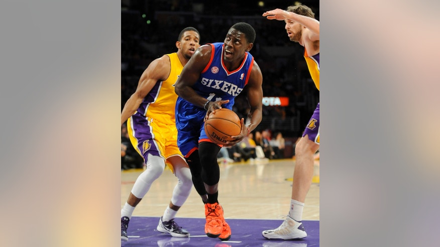 Philadelphia 76ers guard Jrue Holiday, center, gets by Los Angeles Lakers guard Darius Morris, left, and forward Pau Gasol, right, of Spain, as he battles to the basket in the first half of an NBA basketball game, Tuesday, Jan. 1, 2013, in Los Angeles. (AP Photo/Gus Ruelas)
