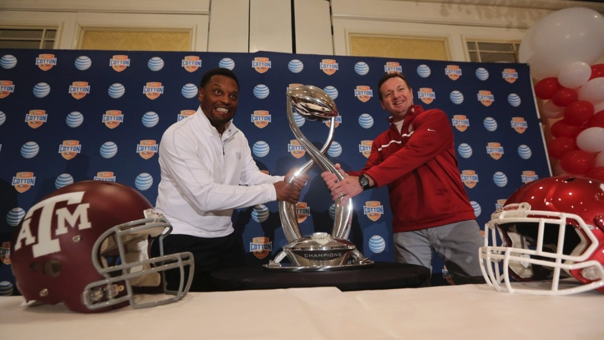 Texas A&M head coach Kevin Sumlin, left, and Oklahoma head coach Bob Stoops pose for photographers pretending to pull at the Cotton Bowl trophy after a news conference leading up to the NCAA college football game Wednesday, Jan. 2, 2013, in Irving, Texas. Before Sumlin became a successful head coach, he was on Stoops' staff at Oklahoma. Before that, they were both assistant coaches recruiting the same area. Now Sumlin takes his Texas A&M team against Stoops' Sooners in a Jan. 4th Cotton Bowl matchup of former Big 12 rivals that are both 10-2. (AP Photo/LM Otero)