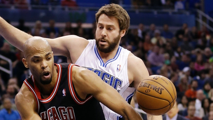 Chicago Bulls forward Taj Gibson, left, loses control of the ball as he tries to shoot in front of Orlando Magic's Josh McRoberts, rear, during the first half of an NBA basketball game, Wednesday, Jan. 2, 2013, in Orlando, Fla. (AP Photo/John Raoux)