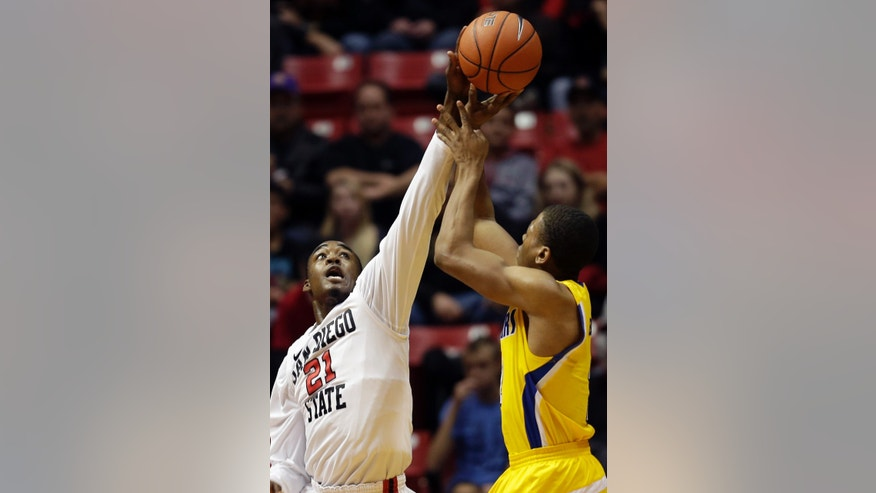 San Diego State's Jamaal Franklin (21) gets a hand up to block a shot by Cal State Bakersfield's Brandon Barnes, right, in the first half during an NCAA college basketball game Wednesday, Jan. 2, 2013, in San Diego. (AP Photo/Gregory Bull)